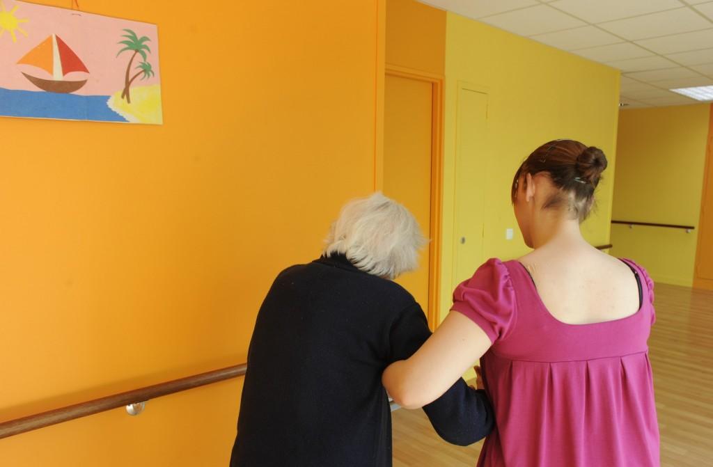 Une résidente accompagnée par un soignant